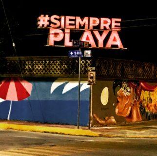 "An electric sign on a darkened street corner reads ""#SiemprePlaya."""