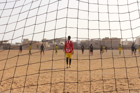 View of a game unfolding on a soccer pitch from behind the goal's net, with the goalkeeper in red standing on the other side.