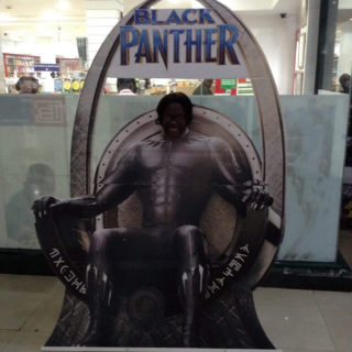 Woman puts her head in life-sized cut out from the Black Panther movie.