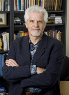 Portrait of a gray-haired man in front of a bookshelf.