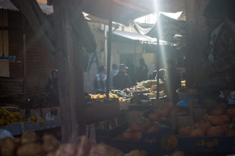 Fruit and vegetable stalls in a shaded market with sunlight beaming through the awnings covering the stalls.