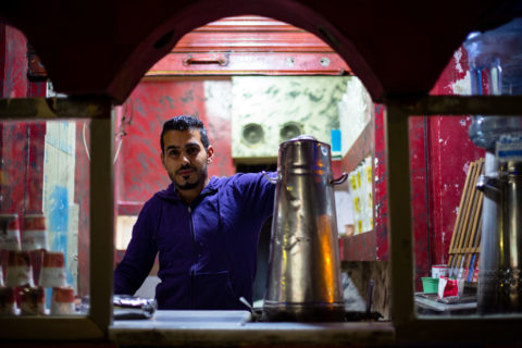 Man stands behind a large coffee pot in a small, red-walled shop.