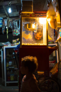 Light from the popcorn cart illuminates the dark passage way, showing children and the popcorn maker.
