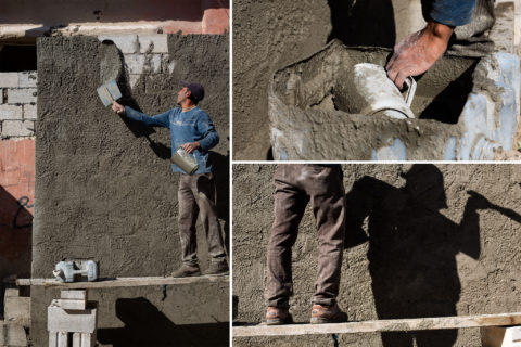 Man on wooden platform coats a brick wall in cement.