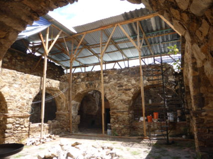 The courtyard of A courtyard with stone archways and an overhang metal, with sunlight streaming down through the center.
