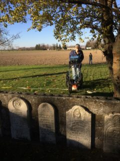 A young person moves over grass near farmland with a radar device, all behind four unmarked gravestones.