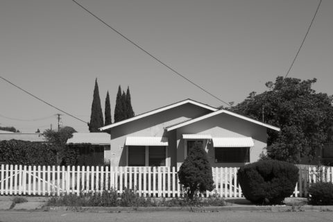 House behind a white-picket fence.