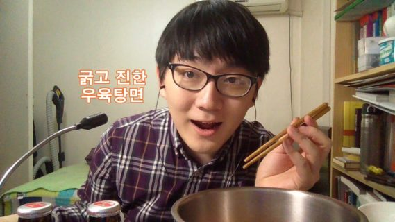 A young man holding chopsticks leans over a large phone bowl on the right, with a microphone jutting into the frame on the left.