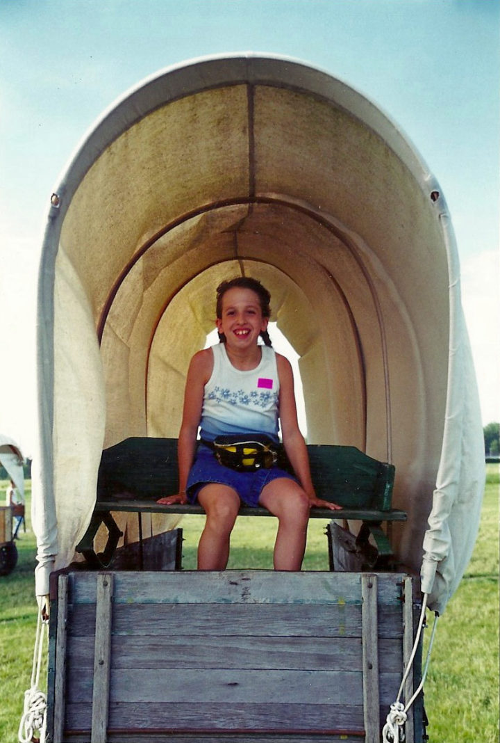 Laura Heath-Stout is portrayed as a child in this photograph, seating on an old wagon, looking happy.