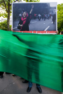 The sihlouette of a demonstrator behind a plain green banner holds a sign up over it.