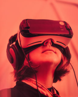 Close up of a woman with a VR headset on, her face tilted skward.