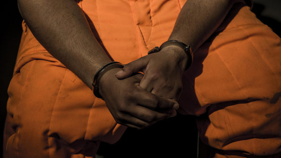 Close up of hand-cuffed hands resting in the lap of a man who is wearing an orange prison jumpsuit.