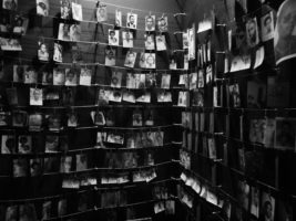 A black and white photo of a room where people hang photographs of their loved ones. There are over 12 rows of photos, from floor to ceiling, clipped to strings that run from wall to wall.