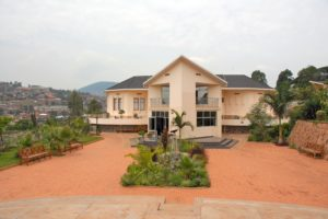 The Kigali Genocide Memorial, a building painted in cream color, surrounded by gardens providing a place for quiet contemplation about the history of the Genocide against the Tutsi.