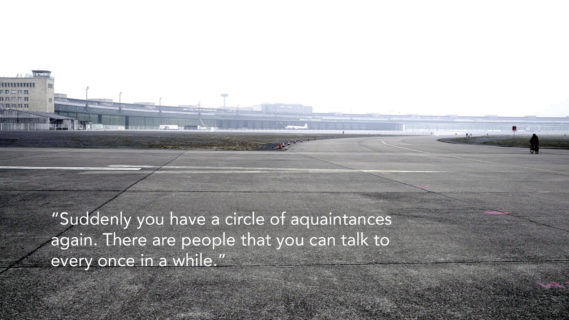 "Photo shows an airport terminal taken from an empty road. The text on the photo, a quote from an interlocutor, reads: ""Suddenly you have a circle of aquaintances again. There are people that you can talk to every once in awhile."""