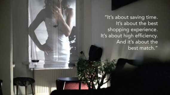 "A photo of a woman taking a selfie of herself in the mirror, and figure-hugging sleeveless dress is projected onto the window shade of a small darkened apartment. The text in the photo, a quote from an interlocutor, reads: ""It's about saving time. It's about the best shopping experience. It's about high efficiency. And it's about the best match."""