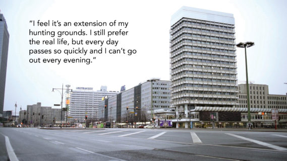 """A photo of a four-lane, two-way street, with a row of office buildings fading into the distance. The text in the photo, a quote from an interlocutor, reads, """"I feel it's an extension of my hunting grounds. I still prefer the real life, but everyday passes so quickly and I can't go out every night."""""""