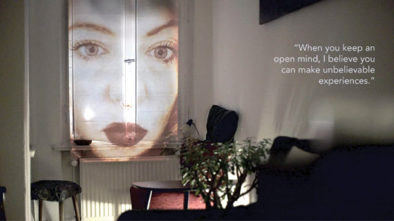 "A woman's face is projected onto the window shade of a small darkened apartment. The text in the photo, a quote from an interlocutor, reads: ""When you keep an open mine, I believe you can make unbelievable experiences."""