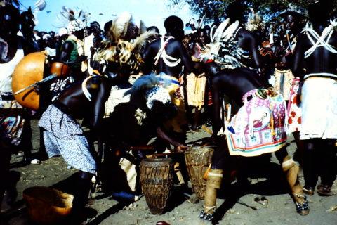 Men in the foreground enthusiastically lean over to play drums. On the other side of them a circle of men in ritual garb dance.