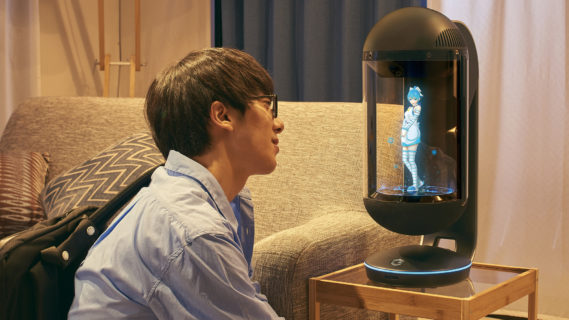 A young man in glasses sits on the floor in front of a small endtable that's beside a sofa. Entranced, he looks at a character projection of Azuma Hikari. She's about 10 inches tall, wearing a holter top white dress, with above the knee white and blue striped socks, and she strikes a flirtatious pose.