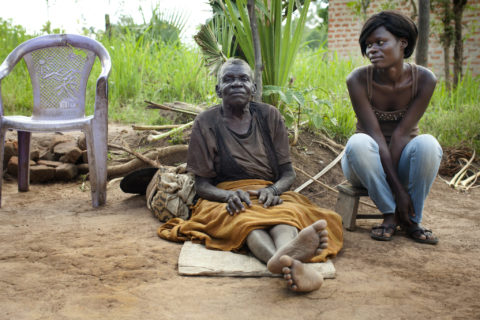 A Grandmother sits on a mat outside, her legs extended. On her left side, her grown grandaughter sits on a short stool.