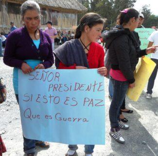 """Two young women hold a sign that reads, """"Senor presidente, si esto es paz, que es guerra?"""""""