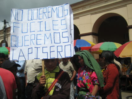 "A young boy holds a sign that reads, ""No queremos fuciles queremost lapisero."""