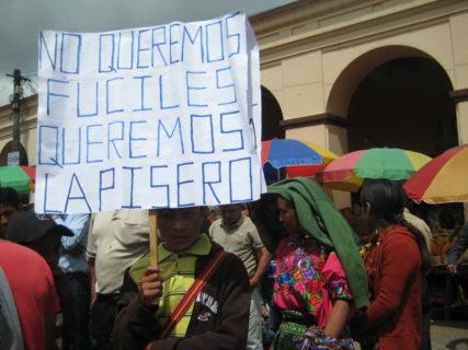 "A young boy holds a sign that reads, ""No queremos fuciles queremost lapisero."""