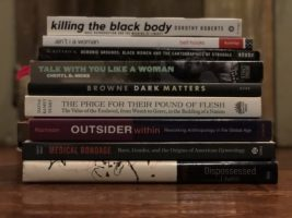 Stack of books lying on a table written by black women including Dorothy Roberts, Bell Hooks and Cheryl D. Hicks