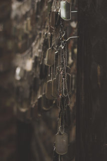 Tens if not hundreds of dogtags hang from small hooks on a wall