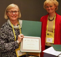 Photo of Katherine Verdery and Helena Wulff holding the Victor Turner Prize. Verdery holds the award in her hand.