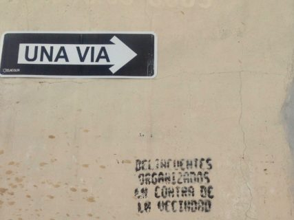 """Cement wall with a street sign reading """"una via"""" (one way) affixed to it. The stencil is written below."""