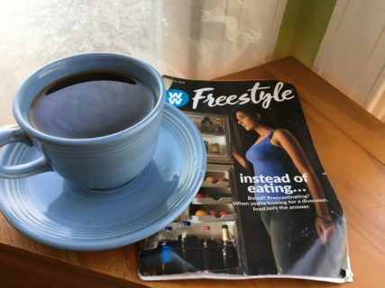 Close up of a cup of coffee and a weight loss brochure, which shows a woman looking into an open refrigerator.