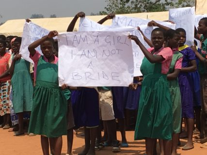 "Two girls in identical school uniforms hold up a sign that reads ""I am a girl. I am not a bride."""