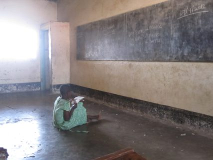A female student sits on the floor of a classroom, looking up at a chalkboard and taking notes.