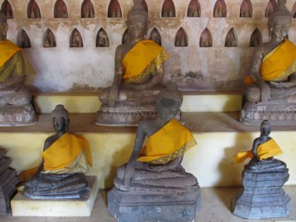 Photo shows six Buddha statues, three on a raised platform and three below. A scarf is draped over the left shoulder and wrapped under the right arm of each statue.