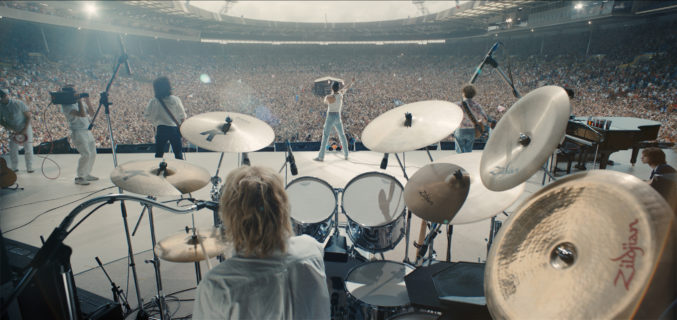 Scene of Queen's Live Aid concert that looks out from behind the drummer to show Freddy Mercury singing before a sold out stadiem.