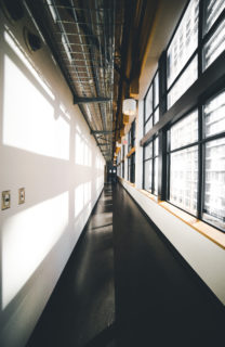 Empty university hallway, with tall windows on the right side.