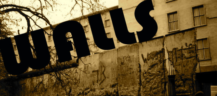 """An old photo of a section of the Berlin wall that is weathered and cracked, with what looks like an apartment building behind it. The word """"Walls"""" is written across the top of the photo."""