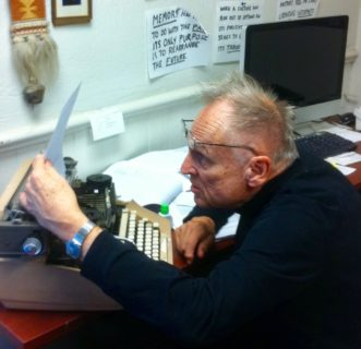 Roy Wagner sits in front of a typewriter, glasses perched on his forehead, leaning into the piece of paper that he's holding up to read.