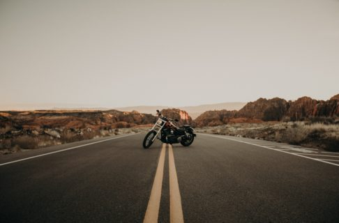 A motorcycle is parked in the middle of an empty desert road