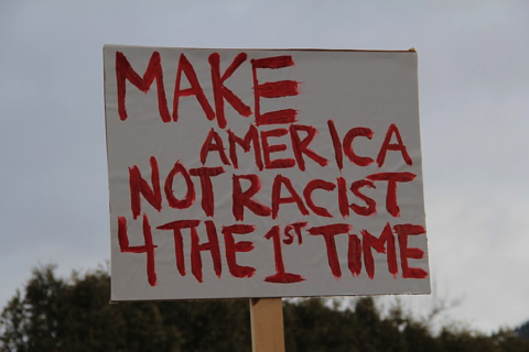 Sign with handpainted letters reads 'Make America Not Racist 4 the 1st Time'.