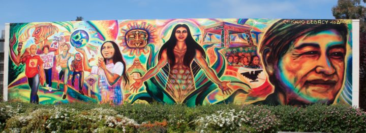 Large mural. In the center a woman emerges from the bud of a flower, her arms outstretched and welcoming the iblookers. Ancient Mayan and Aztec pyramids and suns apear in the background. In the fore ground are Latinx youth marching and playing.