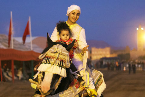 Lilia, no more than three years old, sits in front of Amal atop a horse. Decorative tassels cover the horse's eyes.