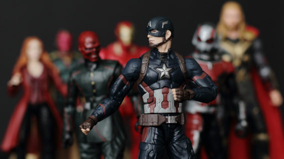 An action figure of Caption American stands front and center, posed with his fists clenched and ready to fight. Behind him and slightly out of focus, stand other action figures from the Marvel Universe