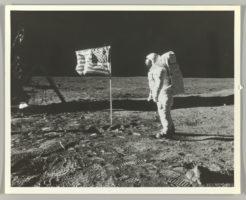 Astronaut Buzz Aldrin next to US flag on lunar landscape.