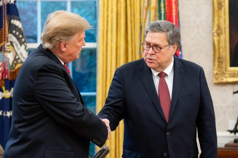 President Trump and Attorney General William Barr stand in the Oval Office, shaking hands.