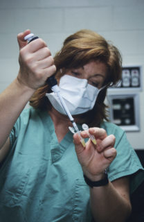 A woman in scrubs and wearing a surgical mask, injects fluid into a small tube held by her thumb and index finger. She has another tube clutched between her index finger and middle finger.