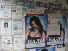 A photo of Bulgarian nekrologs on a wall with other postings nearby, most noticeably an upcoming performance by a female singer.