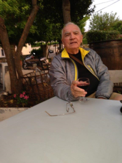 Photo of William P. Mitchell sitting at a patio table with a full glass of wine in his hand.
